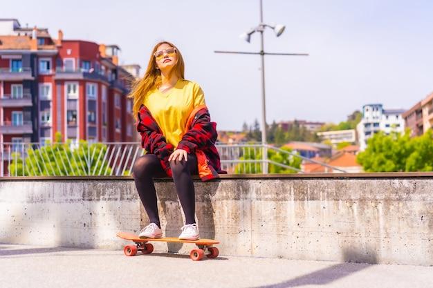 Skater donna in una t-shirt gialla, camicia a quadri rossa e occhiali da sole, seduta con lo skateboard su una panchina in città