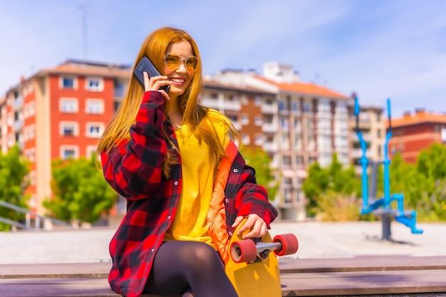 Skater donna in una t-shirt gialla, camicia a quadri rossa e occhiali da sole, seduta con lo skateboard in città, chiamando con il telefono