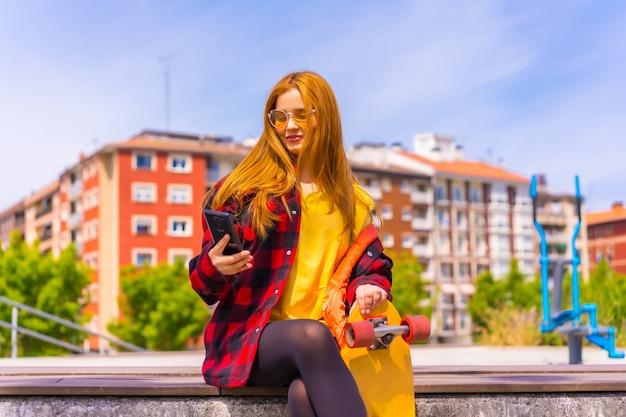 Skater donna in una t-shirt gialla, camicia a quadri rossa e occhiali da sole, seduta con lo skateboard in città, sorridente che chiama con il telefono