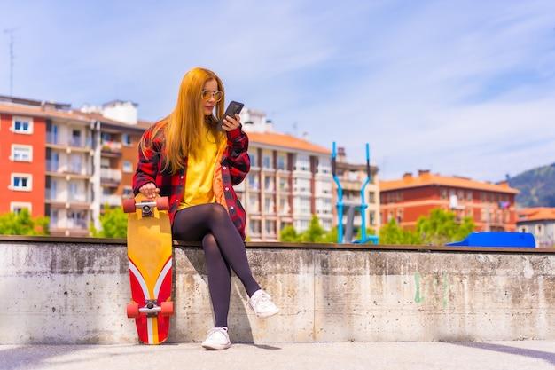 Skater donna in una t-shirt gialla, camicia a quadri rossa e occhiali da sole, seduta con lo skateboard in città inviando un messaggio audio con il telefono