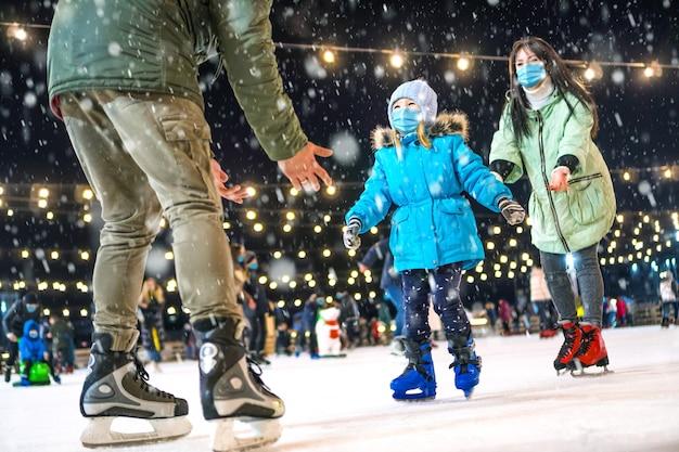 Pista di pattinaggio. famiglia che indossa le maschere mediche sulla pista di pattinaggio