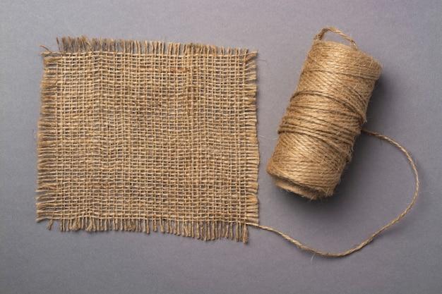 Una matassa di filo di lino e un lembo di tessuto di lino su un grigio