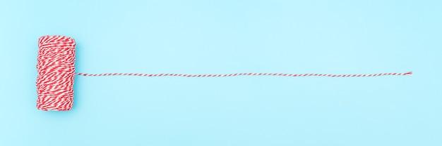 Matassa di spago rosso e bianco per il confezionamento di regali di natale e capodanno, scatole, pacchi su sfondo blu