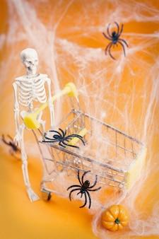 Scheletro con una zucca vicino alle ragnatele e ai ragni del carrello su uno sfondo arancione