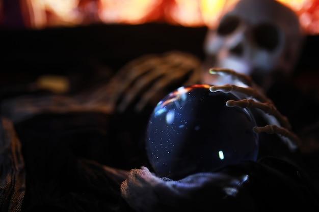 Scheletro zombie mano che sorge da un cimitero - halloween. misteriose previsioni della palla magica e fumo sulla scena oscura. indovino, potere mentale, concetto di previsione. sfondo misterioso