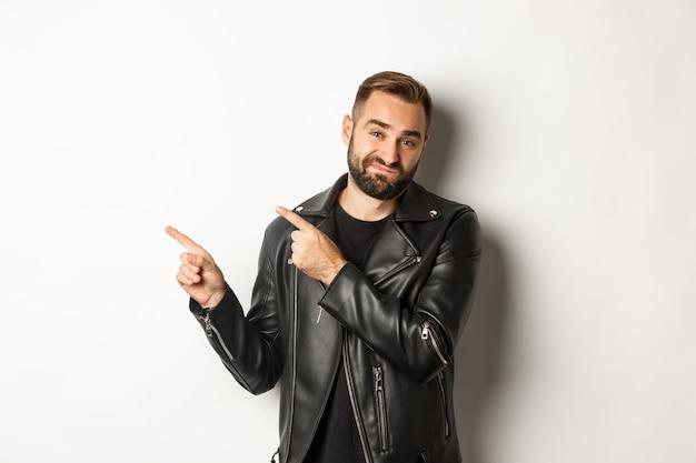 Scettico e scontento uomo in giacca di pelle, puntando le dita nell'angolo in alto a sinistra, mostrando una cattiva offerta promozionale, in piedi su sfondo bianco riluttante.