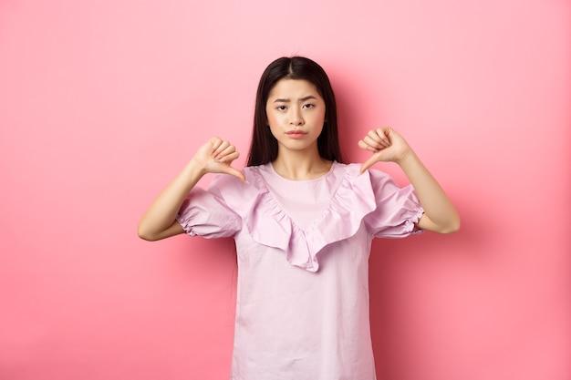 Donna asiatica scettica e delusa che mostra i pollici verso il basso con sorrisetto riluttante, antipatia per il prodotto, mostra emozioni negative, in piedi su sfondo rosa.