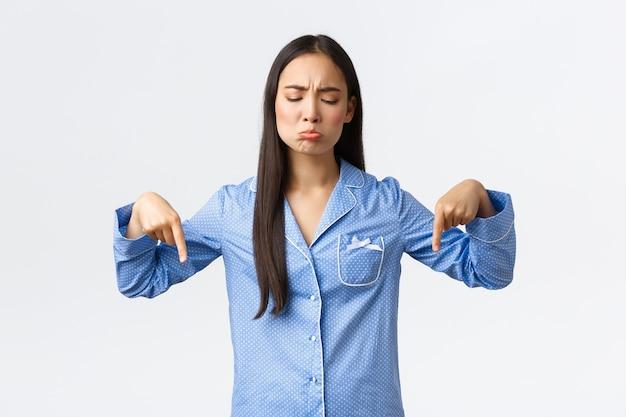 Ragazza triste imbronciata scettica e delusa in pigiama che punta e guarda in basso. donna dispiaciuta, che si lamenta della cattiva qualità del prodotto, che mostra qualcosa di sconvolgente, sfondo bianco.