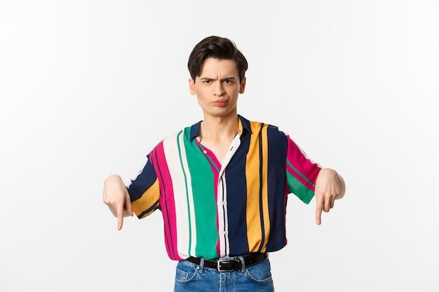 Uomo queer scettico e scontento che punta il dito verso il basso, fa una smorfia e giudica qualcosa di brutto, in piedi sopra il bianco.