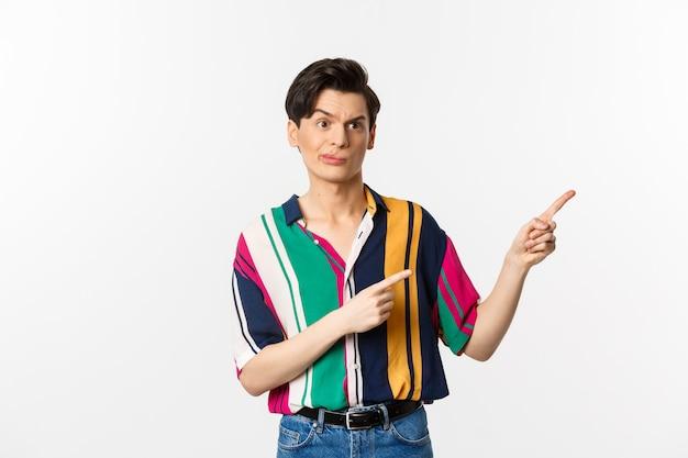 Uomo gay scettico che fa una smorfia delusa, puntando il dito verso il cattivo prodotto, in piedi sopra il bianco