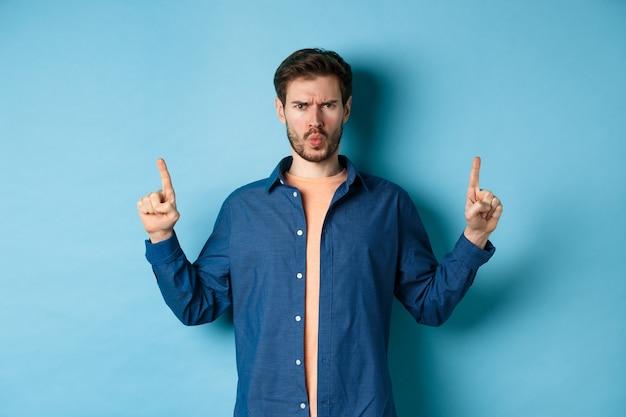 Giovane scettico che aggrotta le sopracciglia, punta il dito verso l'alto e si lamenta, sembra deluso o infastidito, in piedi su sfondo blu.
