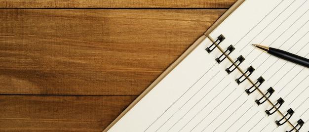 Blocco note di schizzo e una penna su fondo di legno con lo spazio della copia. taccuino vuoto vista dall'alto