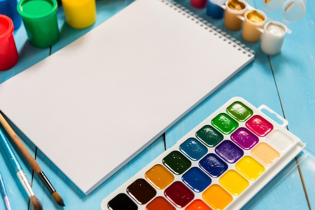 Sketchbook e acquerelli con gouache su sfondo blu.