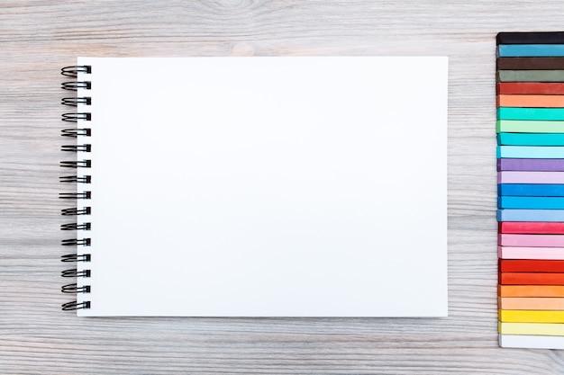 Sketchbook con un foglio bianco e alcuni colori