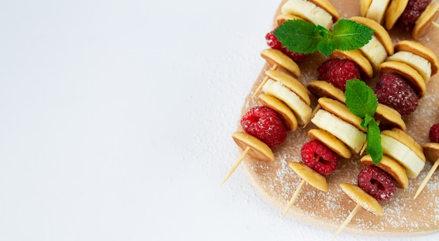 Spiedini con pancake, lamponi, banana, foglie di menta e zucchero in polvere isolati su sfondo bianco. impacco a buffet per dessert