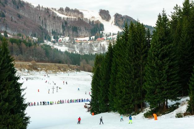 Stazione sciistica in una bella giornata invernale; sciatori e snowboarder che sciano lungo il pendio fino alla base di una seggiovia; alberi e montagne