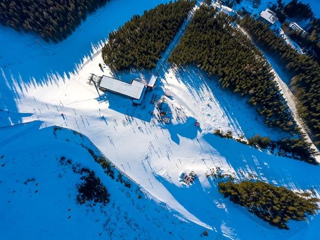 Stazione sciistica con tempo soleggiato. pista da sci di una montagna boscosa. molti turisti vicino alla stazione degli impianti di risalita e al bar. vista aerea