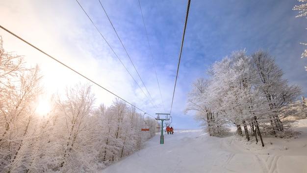 Stazione sciistica, vacanze invernali. meraviglioso paesaggio montano sulla pista da sci accanto all'impianto di risalita all'alba.