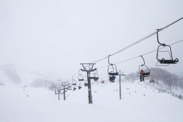 Sciare nella stagione invernale, montagne e attrezzatura da sci sulla pista da sci