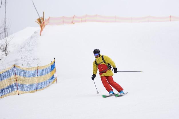 Sciatore con lo zaino in spalla scendendo in discesa con gli sci