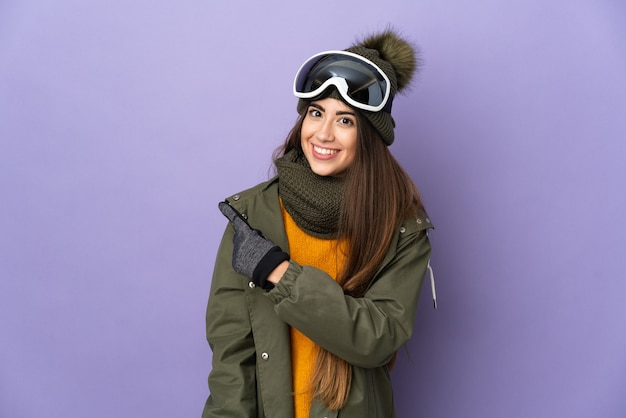 Ragazza caucasica sciatore con occhiali da snowboard isolati su sfondo viola che punta di lato per presentare un prodotto