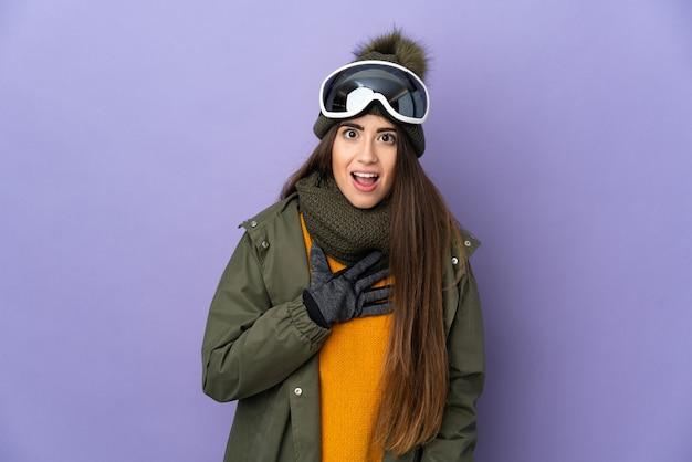 Ragazza caucasica sciatore con occhiali da snowboard isolato su sfondo viola sorpreso e scioccato mentre guardava a destra