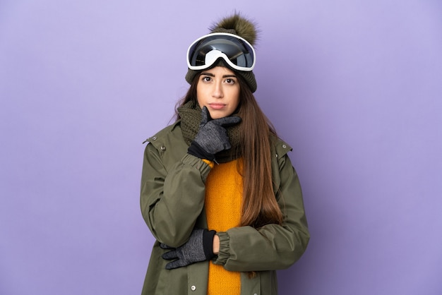 Ragazza caucasica sciatore con occhiali da snowboard isolato su sfondo viola pensando