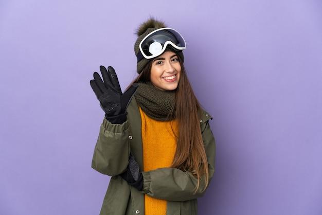 Ragazza caucasica sciatore con occhiali da snowboard isolato sulla parete viola contando cinque con le dita