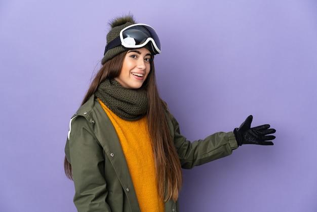 Ragazza caucasica dello sciatore con occhiali da snowboard isolati sulla parete viola che estende le mani a lato per invitare a venire