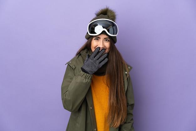 Ragazza caucasica dello sciatore con occhiali da snowboard isolati sulla parete viola felice e sorridente che copre la bocca con la mano