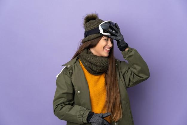 La ragazza caucasica dello sciatore con gli occhiali da snowboard isolati sulla parete viola ha realizzato qualcosa e intende la soluzione