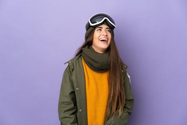 Ragazza caucasica dello sciatore con gli occhiali di snowboard isolati sulla risata viola della parete
