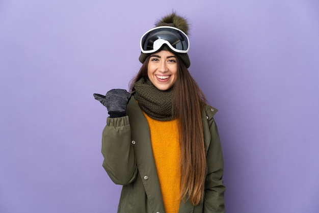 Ragazza caucasica sciatore con occhiali da snowboard isolato sulla parete viola che punta di lato per presentare un prodotto