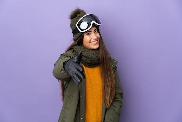 Ragazza caucasica dello sciatore con gli occhiali di snowboard isolati sulla parete viola che agitano le mani per la chiusura di un buon affare