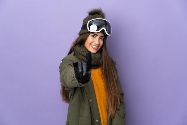 Ragazza caucasica sciatore con occhiali da snowboard isolato sulla parete viola che mostra e alzando un dito