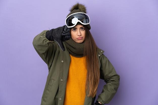 Ragazza caucasica sciatore con occhiali da snowboard isolato sulla parete viola che mostra il pollice verso il basso con espressione negativa