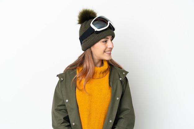 Sciatore donna caucasica con occhiali da snowboard isolati su sfondo bianco guardando al lato e sorridente