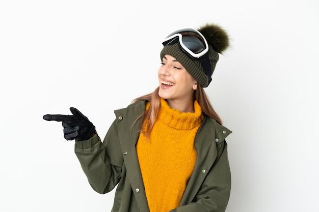 Sciatore donna caucasica con occhiali da snowboard isolati su sfondo bianco che punta il dito di lato e la presentazione di un prodotto
