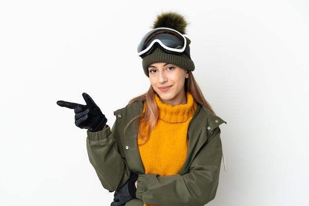 Sciatore donna caucasica con occhiali da snowboard isolati su sfondo bianco che punta il dito a lato