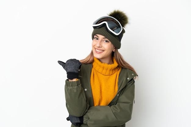 Sciatore donna caucasica con occhiali da snowboard isolati su sfondo bianco che punta di lato per presentare un prodotto