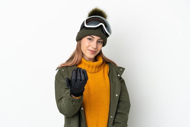 Sciatore donna caucasica con occhiali da snowboard isolati su bianco che invita a venire con la mano. felice che tu sia venuto