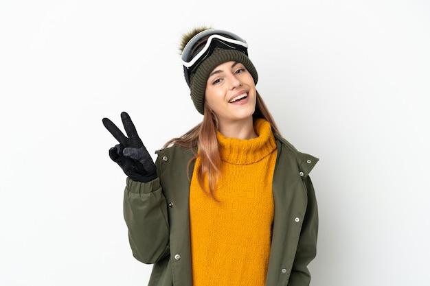 Sciatore donna indoeuropea con occhiali da snowboard isolati su bianco sorridendo e mostrando il segno di vittoria