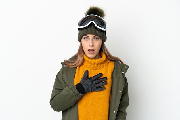 Sciatore donna caucasica con occhiali da snowboard isolati su bianco sorpreso e scioccato mentre guarda a destra