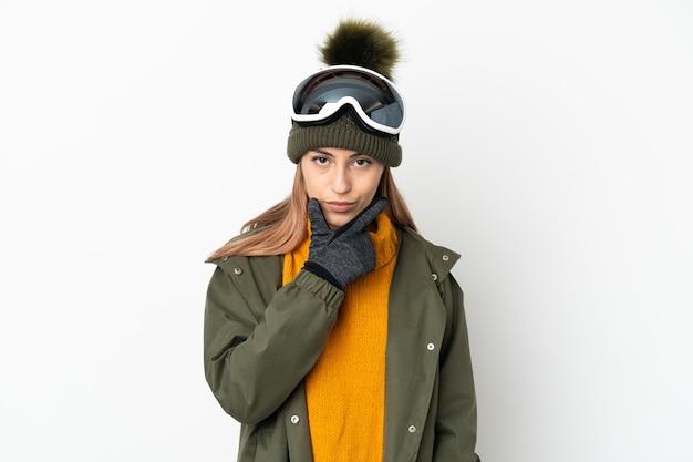 Sciatore donna caucasica con occhiali da snowboard isolato sul pensiero muro bianco