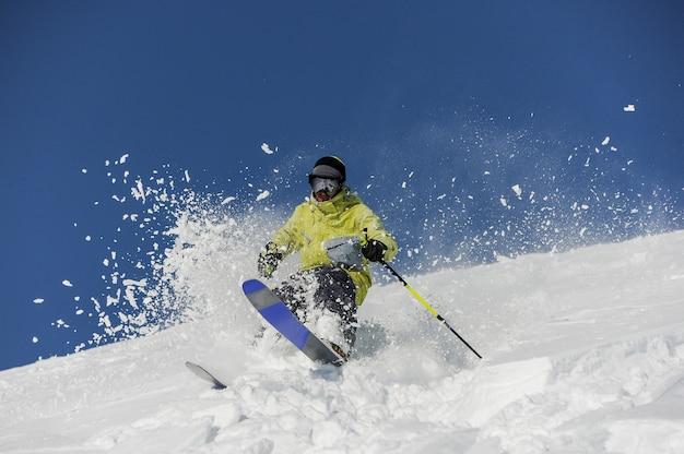 Sciatore vestito in abiti sportivi gialli a cavallo lungo il pendio in georgia, gudauri