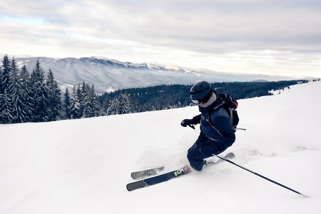 Sciatore inclinazione girando sul picco di una montagna innevata. concetto di sci estremo. vista sulle montagne. cielo grigio su sfondo.