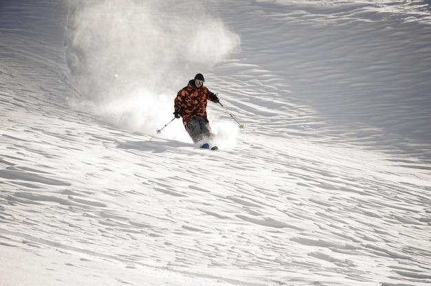 Uomo dello sciatore che guida giù la pista da sci nella località turistica popolare gudauri in georgia