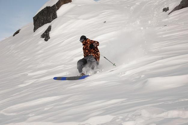 Uomo dello sciatore che guida giù la collina coperta di neve nella famosa località turistica di gudauri in georgia