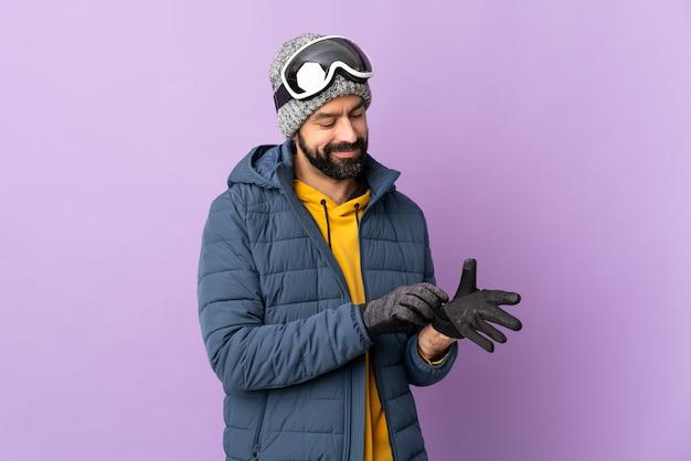 Uomo sciatore con occhiali da snowboard sopra la parete viola isolata