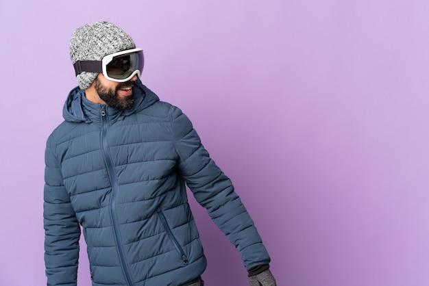 Uomo dello sciatore con occhiali da snowboard su viola isolato